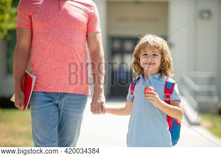 American Father And Son Walking Trough School Park. Kid Elementary Student Carrying Backpacks Holdin