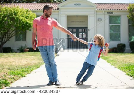Father Supports And Motivates Son. Excited Amazed Kid Going To Primary School.