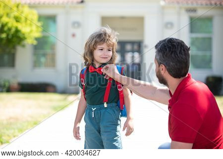 Parent And Pupil Of Primary School. Teacher And Cute Schoolboy With Backpack Near School Park.