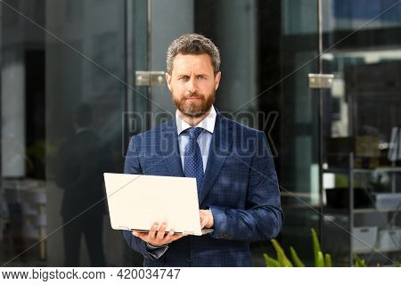 Businessman With Notebook Outdoor. Confident Business Expert. Handsome Man In Suit Holding Laptop Ag