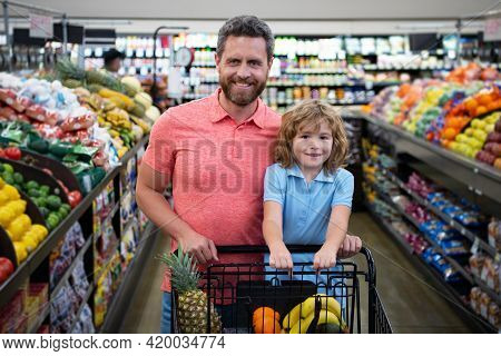 Father And Son With Shopping Basket Purchasing Food In A Grocery Store. Customers Family Buying Prod