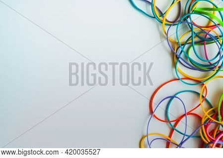Top View Of Colorful Rubber Bands Isolated On White. Rainbow Elastic Rubber Bands On White. Space Fo