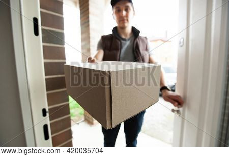 Deliveryman gives the carton box to the customer at the door of his house