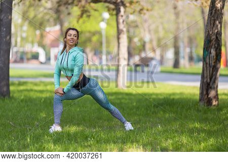 Jogger Woman Stretcing Muscles In City Park Before Workout.