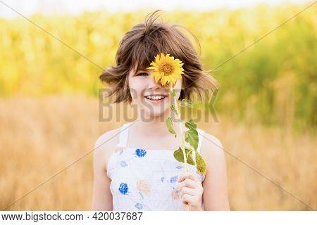 Cute Child Girl Wear Dress With Sunflower In Summer Field. Happy Little Girl Hide Eye With Sunflower