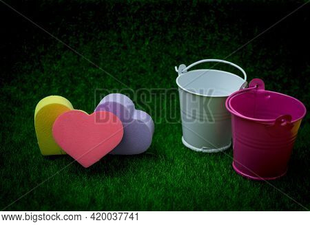 Love Eco Friendly Concept. Colorful Heart Shape With Pink, White Small Bucket On Green Grass Backgro