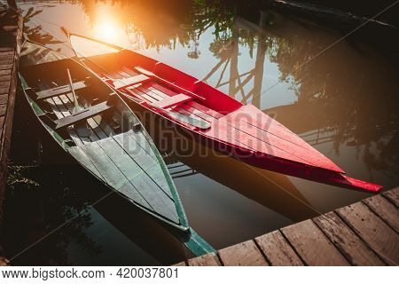 Scenic Nature Landscape Wooden Pier, Moored Boat On Lake. Vintage Old Wooden Red, Green Rowboat Trad