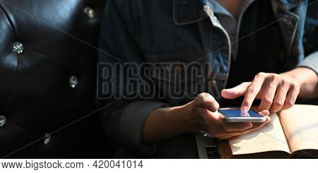 Cropped Image Of Smart Man Hands Holding And Using A White Blank Screen Smartphone While Sitting And