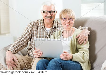 Happy elderly couple talking using laptop together and smiling at camera