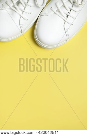 White Sneakers On Yellow Background Top View Flat Lay. Stylish Youth Women's Leather Sneakers, Sport