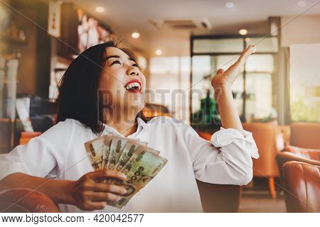Happiness Is Happy. Beautiful Woman Sitting In A Coffee Shop Stretching Her Hands, With A Five Thous