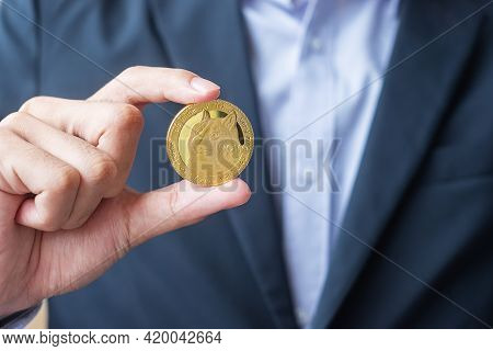 Business Man Hand Holding Gold Dogecoin Cryptocurrency, Crypto Is Digital Money Within The Blockchai