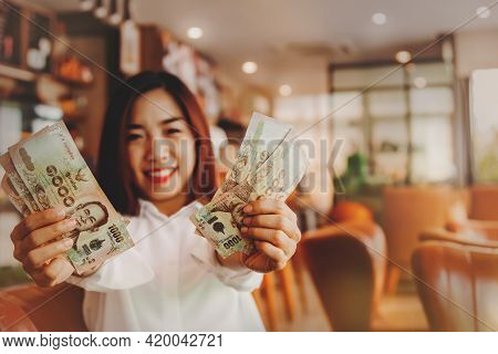 Happiness, A Beautiful Woman Sitting In A Coffee Shop Stretching Her Hands, With A Five Thousand Bah