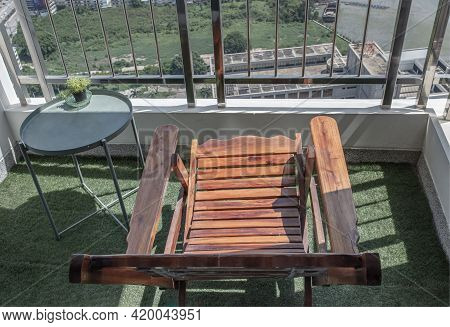 A Wooden Reclining Chair With Small Tree On Side Table With Stainless Steel Balcony Railing Overlook