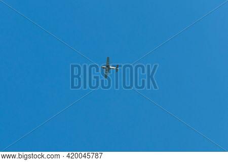 Biplane Flying In A Clear Blue Sky