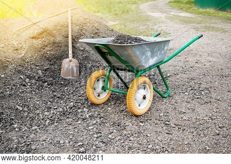 Wheelbarrow With A Shovel And Gravel. As Part Of A Construction Project, A Man Is Transporting Rubbl