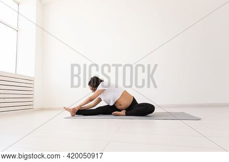 Young Flexible Pregnant Woman Doing Gymnastics On Rug On The Floor On White Background. The Concept