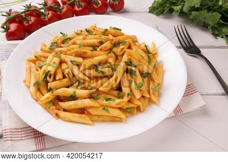 Penne Pasta In Tomato Sauce, Decorated With Parsley On A White Wooden Table, Very Tasty.