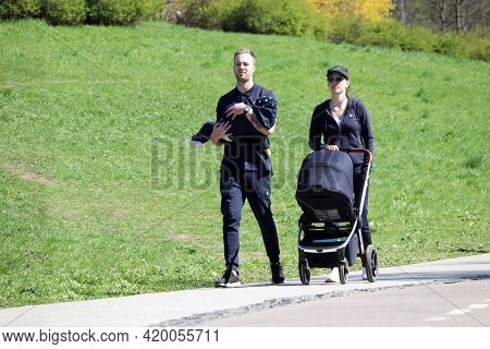 Moscow, Russia - May 2021: Young Couple With Baby And Pram Walking In A Park. Father Carries The Chi
