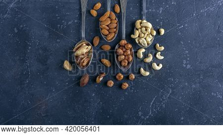 Assortment Of Various Types Of Nuts: Cashew, Hazelnuts, Almonds, Brazil Nuts On Metal Silver Spoons