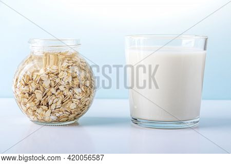 Glass Of Oat Vegetable Milk And Jar With Soaking Oatmeal. Concept Of Making Plant Based Organic Vegg