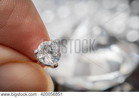 Hand Is Holding Brilliant Or Diamond Gem On Black Background.