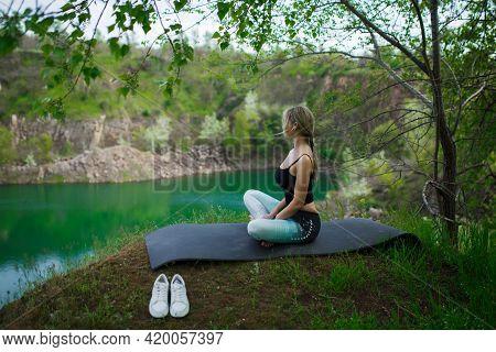 Girl In Sportswear Meditates Near The Lake. Yoga Concession