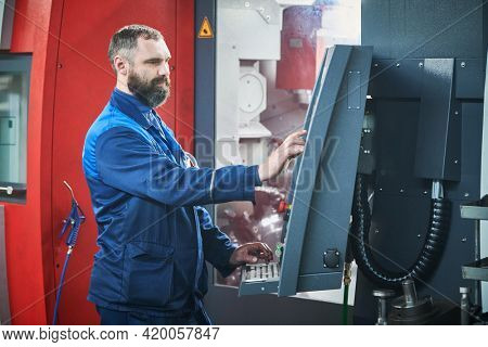 Industrial worker operating cnc machine at metal machining industry