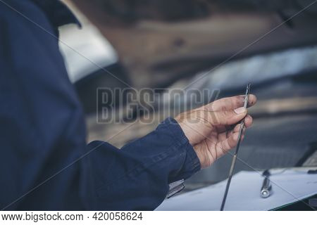 Car Mechanic Man Hand Checking Dipstick Engine Oil Car Mechanical On Site Service. Close Up Hand Man