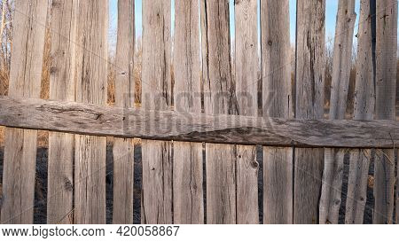 Old Wooden Fence Against Sky With Clouds. Dilapidated Village Fence On A Cloudy Day. Silence And Des