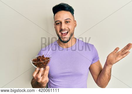 Young arab man holding raisins bowl celebrating achievement with happy smile and winner expression with raised hand