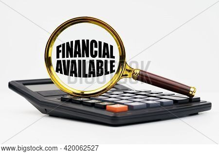 Finance And Business Concept. On A White Background Lies A Calculator And A Magnifying Glass With Th