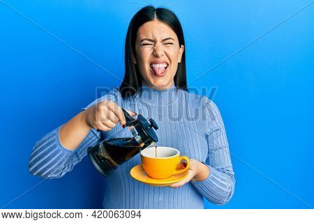 Beautiful brunette woman holding french coffee maker pouring coffee on cup sticking tongue out happy with funny expression.