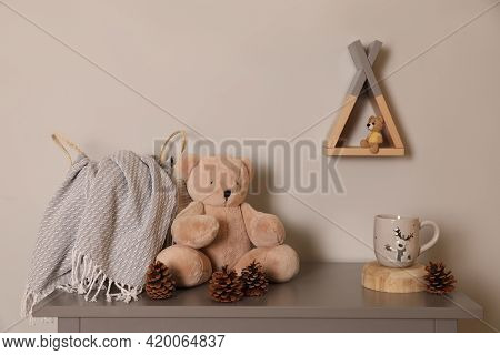 Teddy Bear, Conifer Cones And Drink On Table In Baby Room. Interior Design