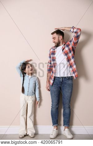 Father And Daughter Comparing Their Heights Near Beige Wall Indoors
