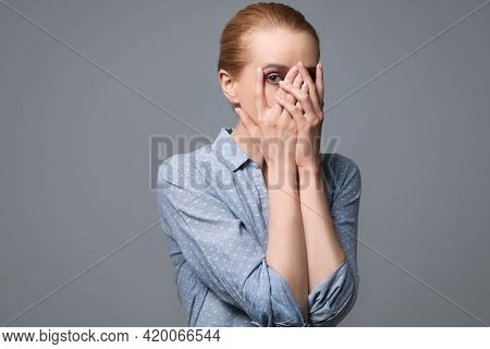 Young Woman Feeling Fear On Grey Background