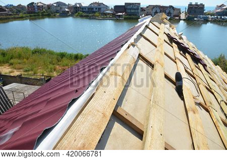 Metal Roofing Construction: A Close-up On An Unfinished Roof Ridge With A Vapor, Moisture Barrier An