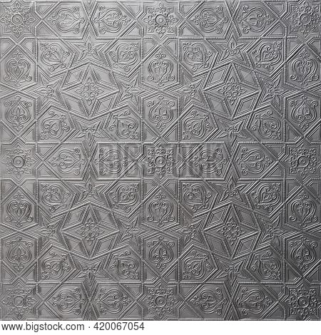 Traditional Islamic Rhythmic Arabesque Pattern In Form Of Embossing On Metal. Textured Gray-silver B