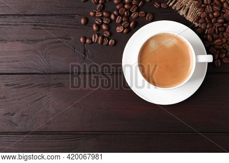 Cup Of Hot Aromatic Coffee And Roasted Beans On Wooden Table, Flat Lay. Space For Text