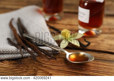 Aromatic Vanilla Extract And Dry Pods On Wooden Table