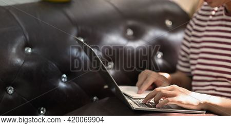 Closeup Creative Man Typing On Computer Laptop That Putting On His Lap While Sitting At The Leather