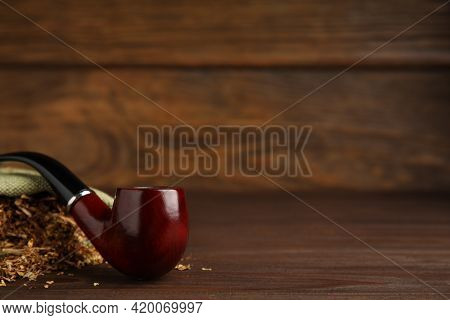 Classic Smoking Pipe With Sack Of Tobacco On Wooden Table. Space For Text