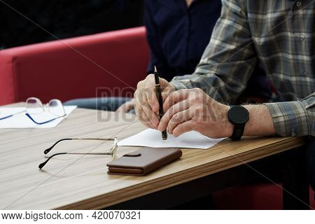 An Adult Man, Sitting At A Table In An Office Or Government Agency, Fills Out Paperwork Or Forms. Th