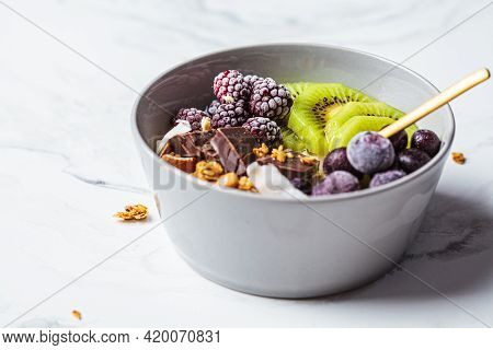 Overnight Oatmeal Bowl With Kiwi, Chocolate, Berries And Tahini, White Marble Background. Healthy Br