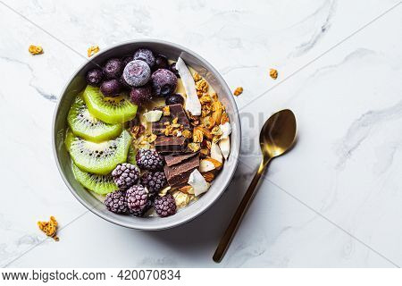 Overnight Oatmeal Bowl With Kiwi, Chocolate, Berries And Tahini, White Marble Background, Top View.,