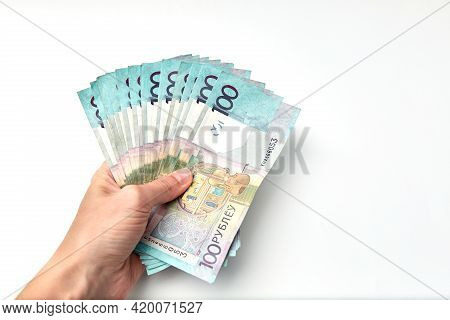 Wad Of Money In Hand Isolated On White Background. Banknote Of One Hundred Belarusian Rubles. Minima