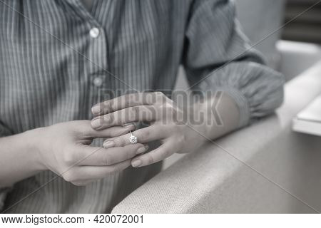 Woman Taking Off Wedding Ring Indoors, Closeup. Cheating And Breakup