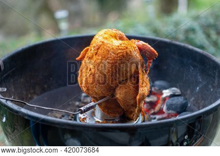 Marinated Chicken On A Chicken Holder With Thermometer On A Barbecue With Glowing Charcoals. Close-u