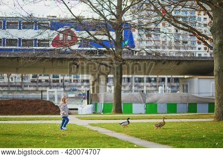 Happy Toddler Girl Running And Chasing Ducks In Andre-citroen Park Of Paris, France