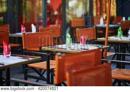 Table Of Traditional Parisian Outdoor Cafe. Empty Restaurant Waiting For Clients In Paris, France